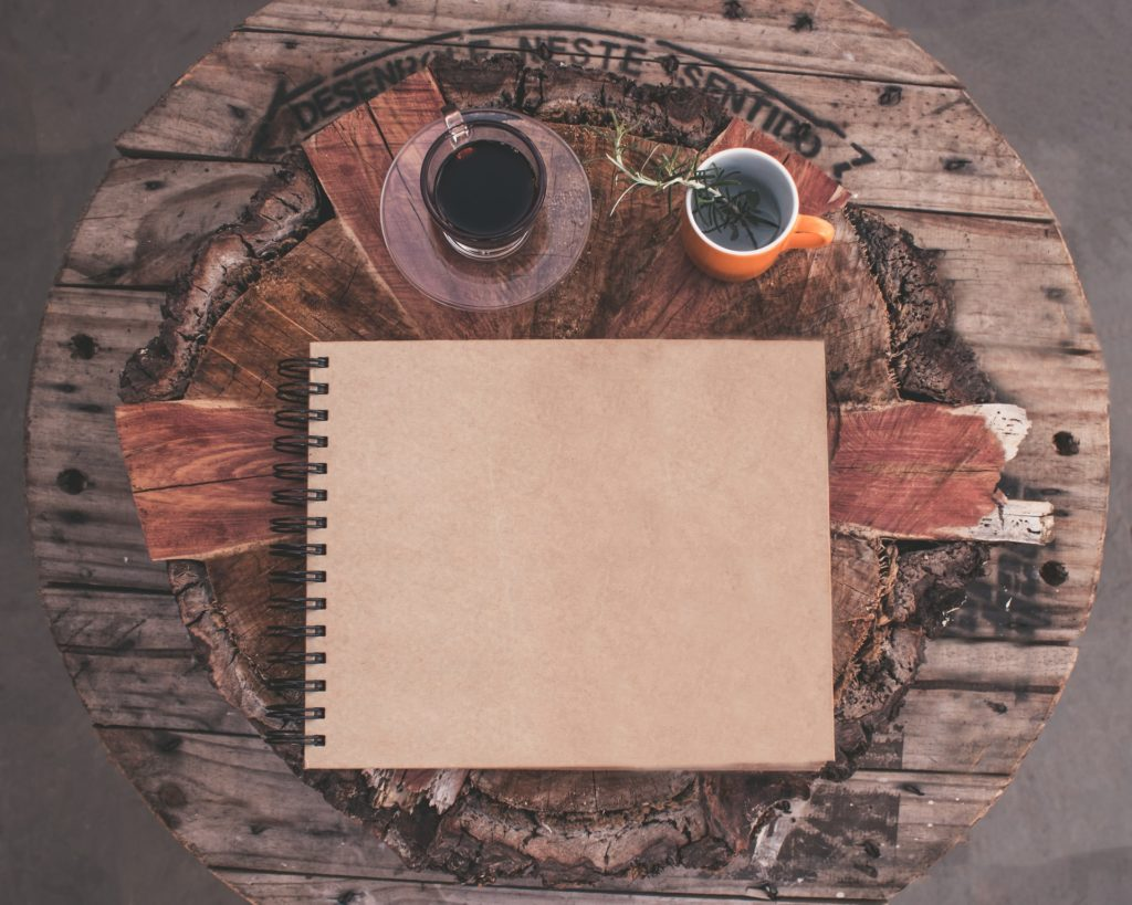 A photo showing a blank notebook on a natural wood table, hinting at the soap nuts instruction booklet that is to come